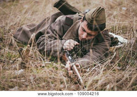 Unidentified re-enactor dressed as Soviet russian soldier reload