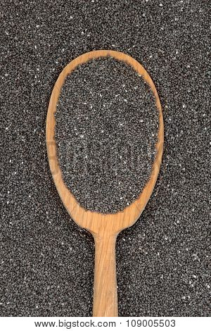 Chia seed health food in an old oak wood spoon and loose forming a background.