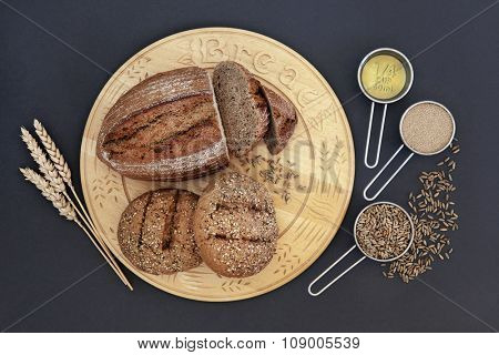 Rye bread loaf and rolls on wooden board with baking ingredients of olive oil, yeast and grain with wheat sheaths