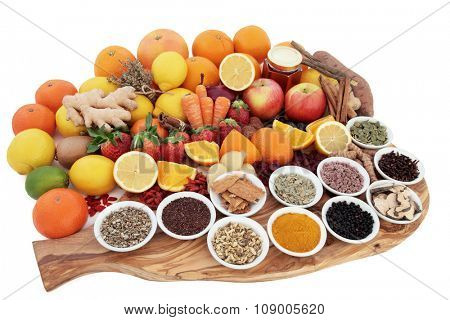 Large food and medicinal herb selection for cold remedy with foods high in antioxidants on an olive wood board over white background.