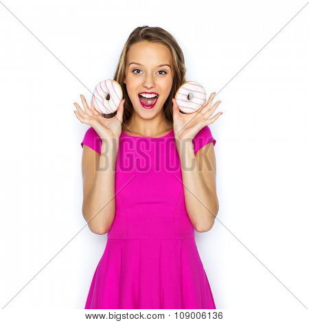 people, holidays, junk food and fast food concept - happy young woman or teen girl in pink dress with donuts