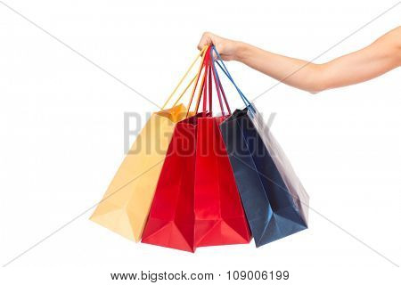 people, consumerism and sale concept - close up of female hand holding shopping bags