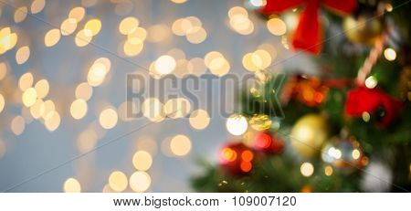 holidays, new year, decor and celebration concept - blurred christmas tree decorated with balls and garland lights background