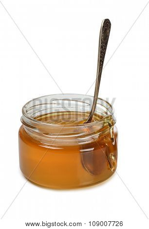 Glass jar with honey on white background