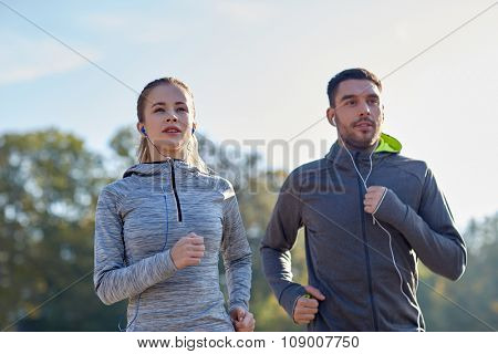 fitness, sport, people, technology and lifestyle concept - happy couple running and listening to music in earphones outdoors