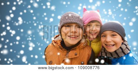 childhood, christmas, winter, friendship and people concept - group of happy kids hugging over snow background