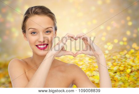 beauty, people, love, valentines day and make up concept - smiling young woman with pink lipstick on lips showing heart shape hand sign over golden glitter or holidays lights background