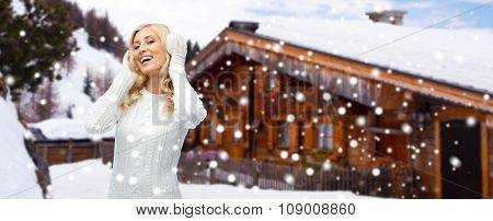 winter, fashion, vacation, christmas and people concept - smiling young woman in earmuffs and sweater over wooden country house and snow background