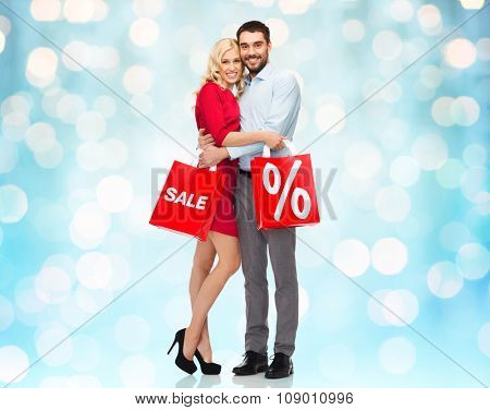 people, sale, discount and christmas concept - happy couple with red shopping bags hugging over blue holidays lights background