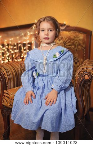 Little girl in a beautiful dress by the fireplace