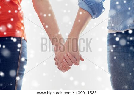 people, homosexuality, same-sex marriage, gay and love concept - close up of happy lesbian couple holding hands over snow effect