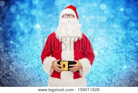 christmas, holidays and people concept - man in costume of santa claus over blue glitter or lights background