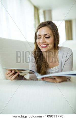 Beautiful Woman On A Sofa Reading A Paper In The Living Room