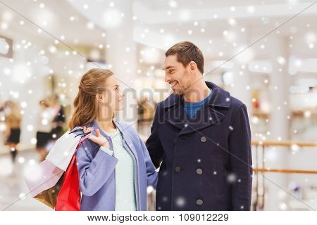 sale, consumerism and people concept - happy young couple with shopping bags talking in mall with snow effect