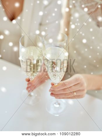 people, homosexuality, same-sex marriage, celebration and love concept - close up of happy married lesbian couple hands holding and clinking champagne glasses over snow effect