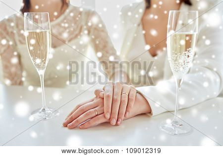 people, homosexuality, same-sex marriage, celebration and love concept - close up of happy married lesbian couple hands on top and champagne glasses over snow effect
