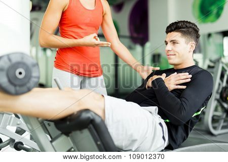 Beautiful Young Woman Instructing A Young Man In The Gym