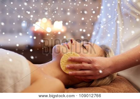 people, beauty, spa, skin care and relaxation concept - close up of beautiful young woman lying with closed eyes and having face massage with sponge in spa with snow effect