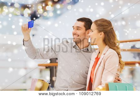 sale, consumerism, technology and people concept - happy young couple with shopping bags and smartphone taking selfie in mall with snow effect