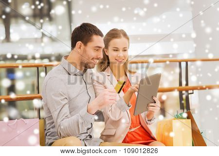 sale, consumerism, technology and people concept - happy young couple with shopping bags and credit card pointing finger to tablet pc computer in mall with snow effect