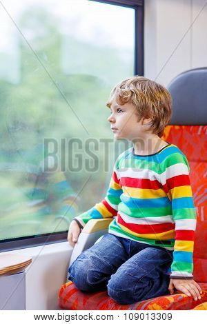 Little boy sitting in train and going on vacations