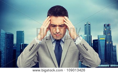 business, people, crisis and fail concept - businessman in suit having head ache over city background