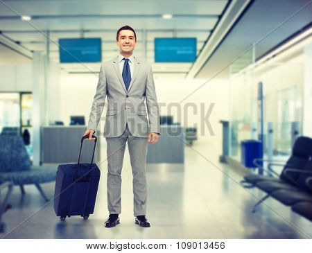 business trip, traveling, luggage and people concept - happy businessman in suit with travel bag over airport background