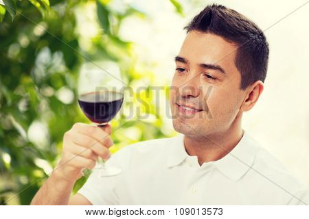 profession, drinks, leisure, holidays and people concept - happy man drinking red wine from glass over green background