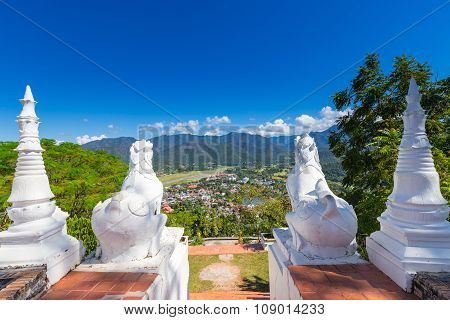 White Thai Art Lions At Entrance Of Wat Phra That Doi Gongmoo With View Of Maehongson City In Evenin