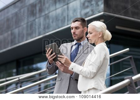 business, partnership, technology and people concept - businessman and businesswoman working with tablet pc computer on city street