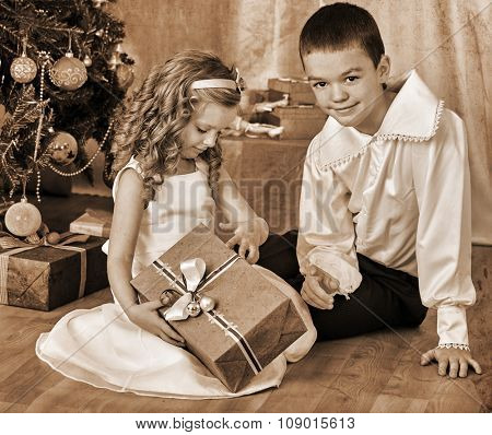 Happy children  brother and sister open gifts under Christmas tree. Black and white retro vintage.