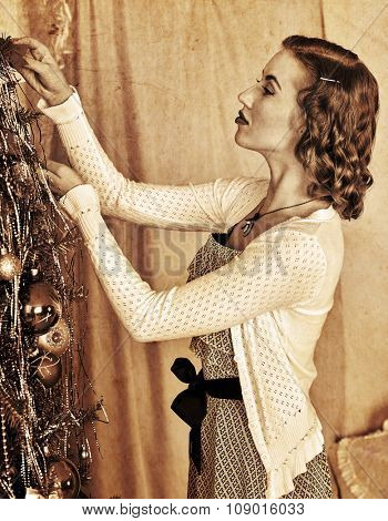 Slim woman dressing Christmas tree. Black and white vintage style.