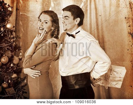 Couple on party flirting near Christmas tree. Man hiding behind a gift. Black and white retro.