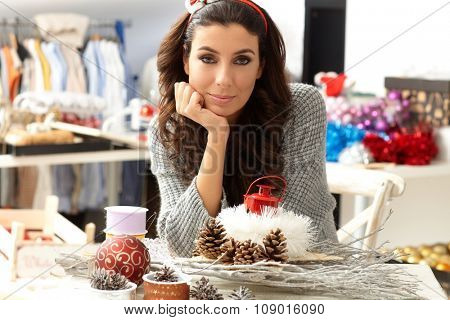 Portrait of young woman making decoration by hand, looking at camera.
