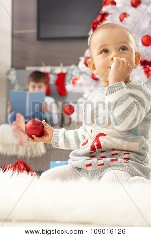 Little girl sitting by christmas tree, playing with ornaments.