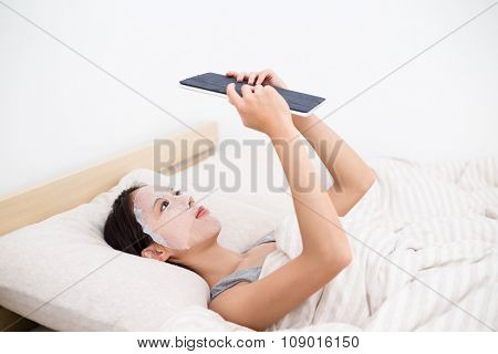 Young woman use of the tablet pc and use of the paper mask