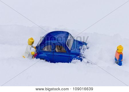 Man pushing car stuck in snow. Toy models.