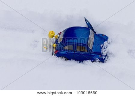 Driver man pushing car stuck in the snow