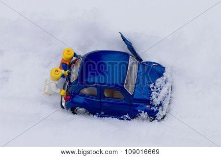 Two men pushing car stuck in snow. Toy models.