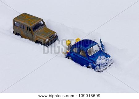 Two men pushing car stuck in a snow.