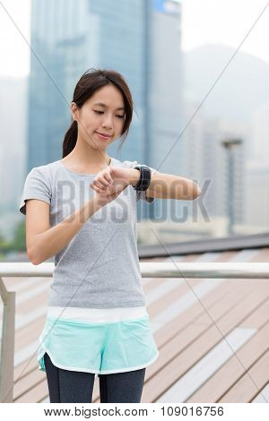 Asian Woman use of the sport watch at oudoor
