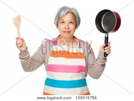 Old woman hold up with cooking tool