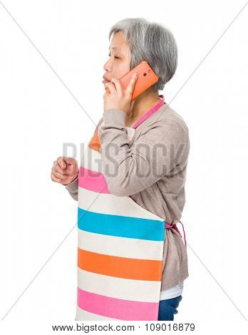 Old woman with apron and talk to someone vis mobile phone