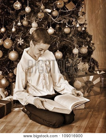 Boy under Christmas tree read old book. Black and white retro vintage.