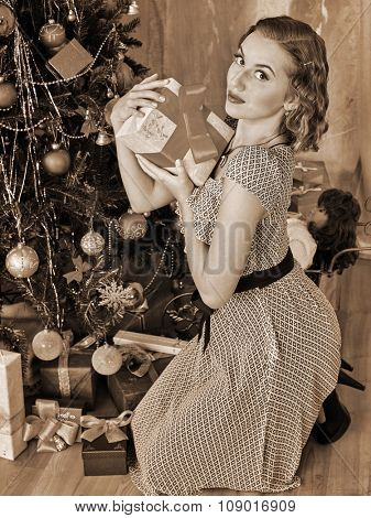 Woman open gift box  under Christmas tree. Black and white retro vintage.