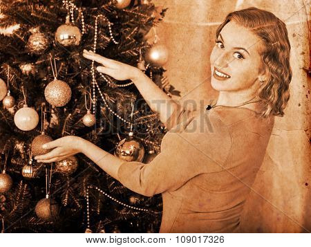 Smiling young woman dressing Christmas tree at home. Black and white vintage.