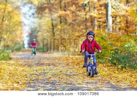 Two little kid boys with bicycles in autumn forest