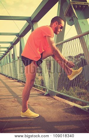 Jogger tying his running shoes.