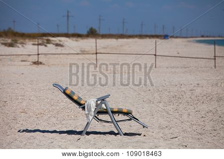 Deck chair with a white scarf on the sandy beach