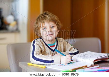 Cute happy schoolkid at home making homework